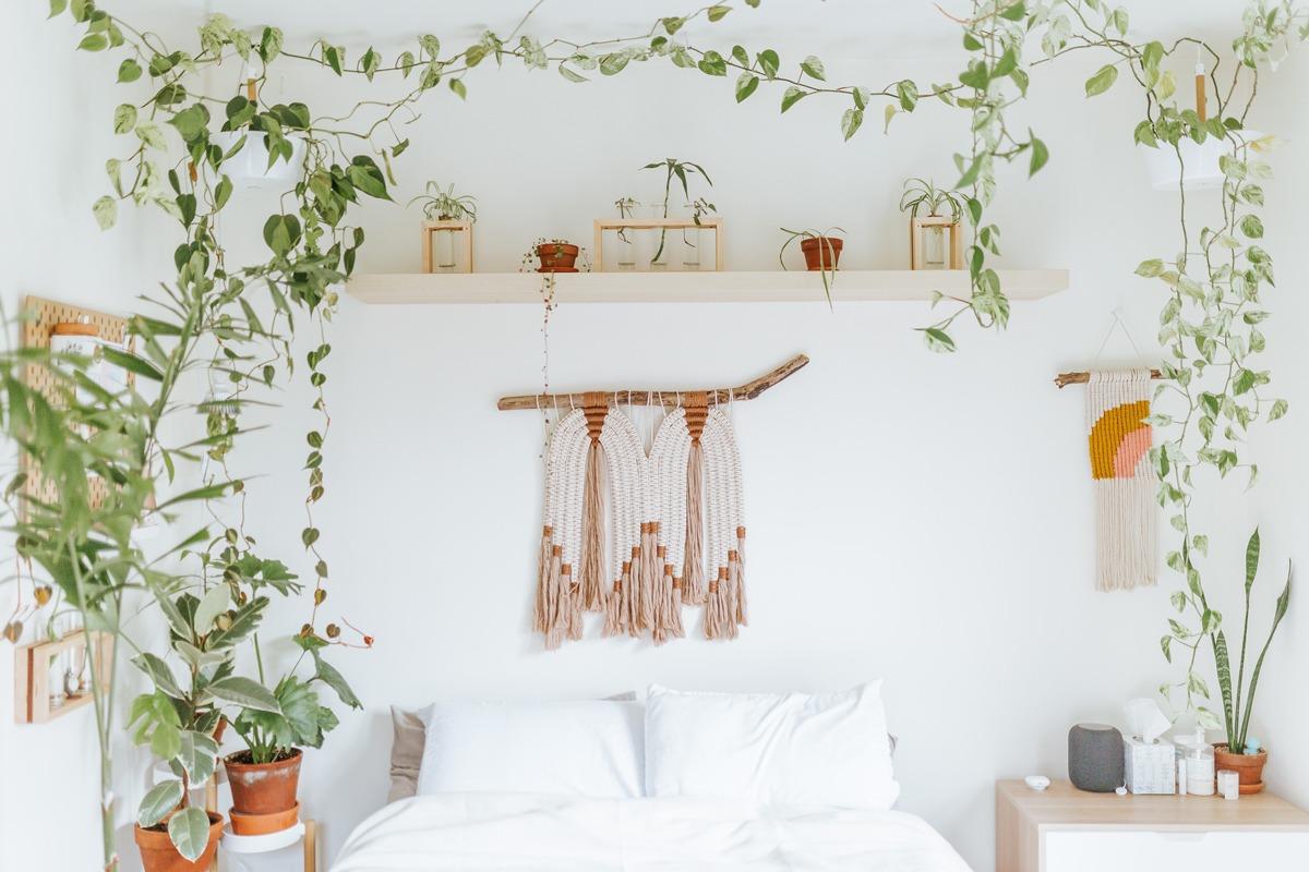 Chambre bohème et naturelle avec plantes et suspensions en macramé